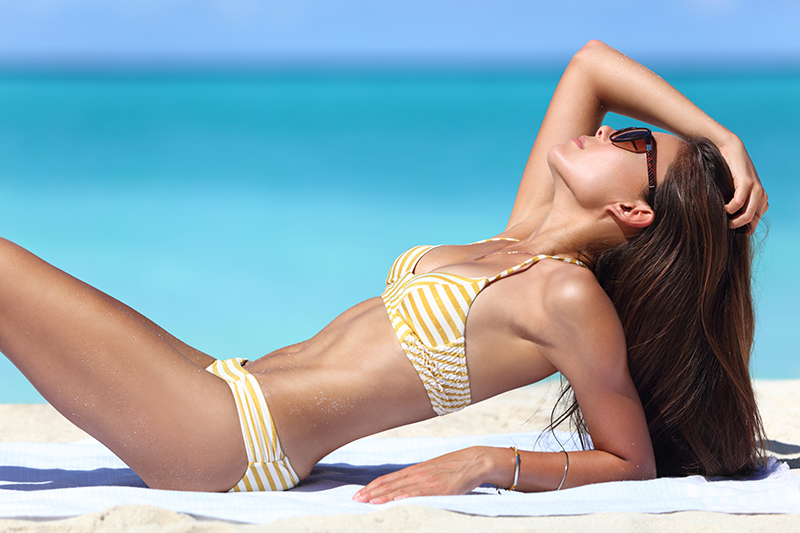 woman with toned abs in yellow and white striped bikini